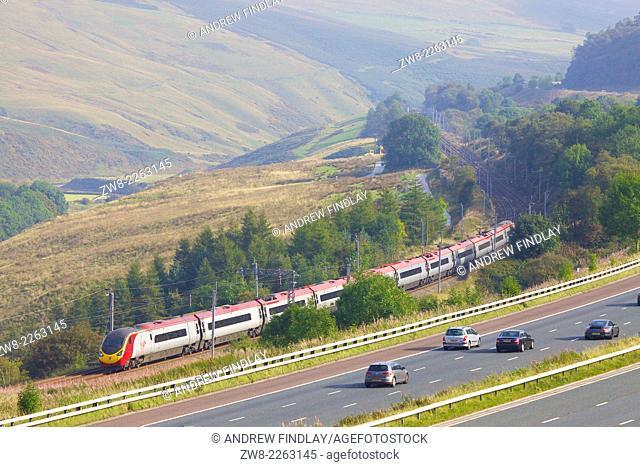 Class 390 Pendolino Virgin train passing the M6 motorway in the River Lune Valley. Howgills, Cumbria, West Coast Main Line, England, UK