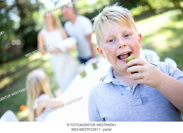 Portrait of boy eating gherkin outdoors with family in background