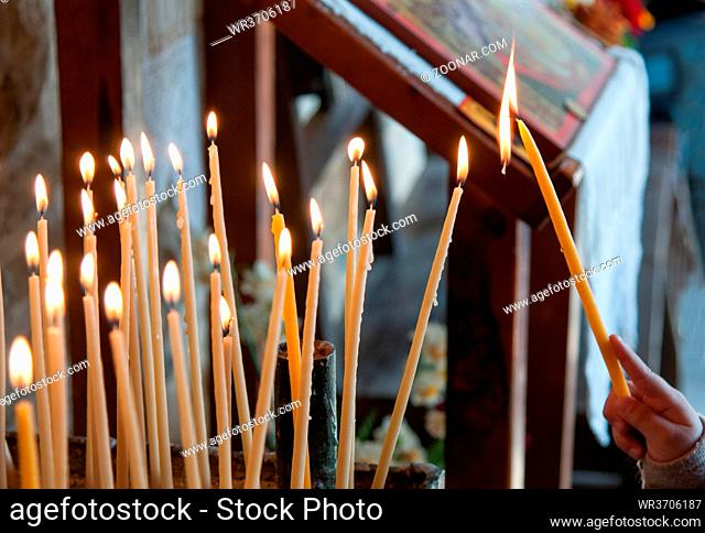 Young teenage fires a church candle for meditation and pray