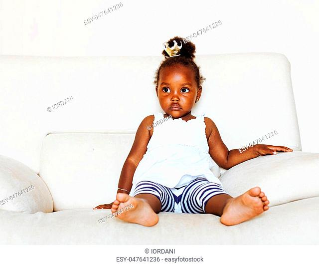 little pretty african american girl sitting in white chair wearing toy crown on head like princess or queen, lifestyle people concept close up