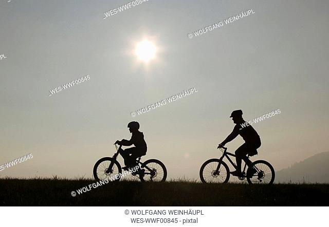 Father and son 10-11 riding mountain bikes, silhouette