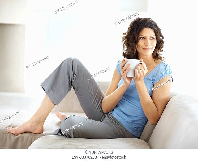 Full length of a smiling young woman having coffee on couch