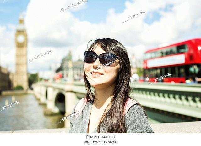 Smiling woman with black hair wearing sunglasses standing on Westminster Bridge over the River Thames, London, with the Houses of Parliament and Big Ben in the...