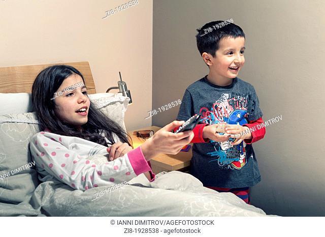 Children watching TV in bed