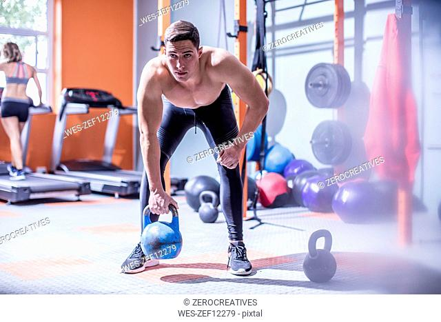 Young man lifting kettlebell in gym
