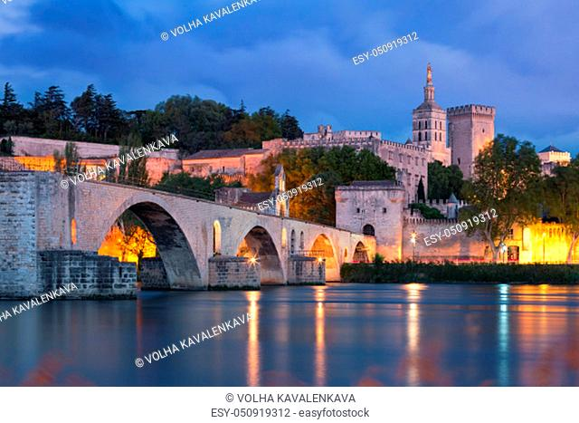 Panoramic view of famous medieval Saint Benezet bridge and Palace of the Popes during evening blue hour, Avignon, southern France
