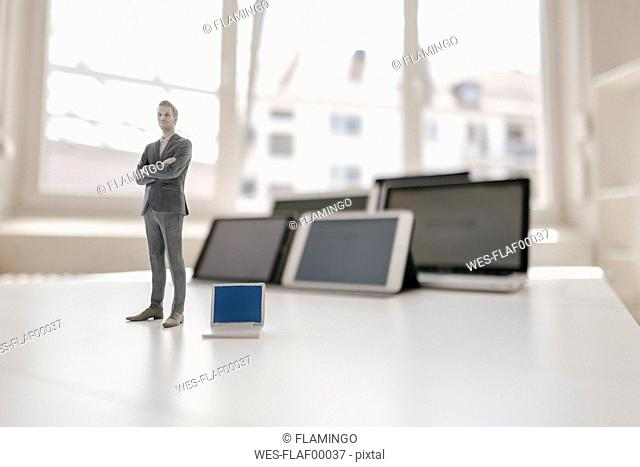 Businessman figurine standing on desk, facing mobile devices