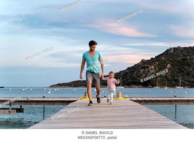 Happy father walking with daughter on a jetty at sunset
