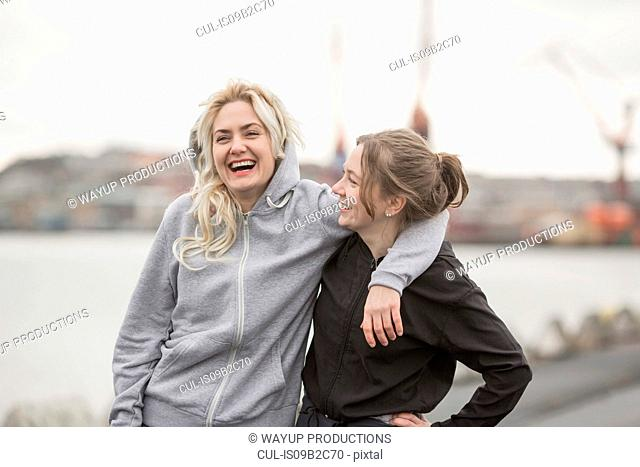 Portrait of two female runner friends laughing on dockside