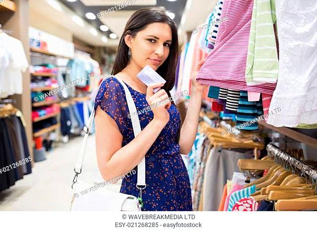 Woman beside clothes display holding credit card in shopping mall