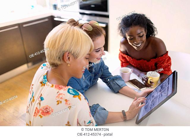 Young women friends using digital tablet at kitchen table