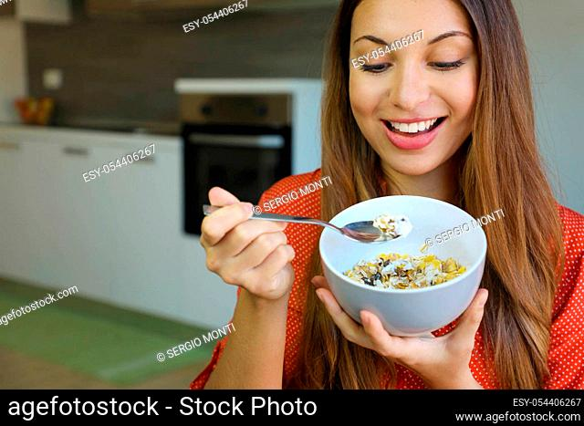 Close up of beautiful young woman eating skyr yougurt with cereal muesli fruit at home, focus on the model eyes, indoor picture. Healthy food concept
