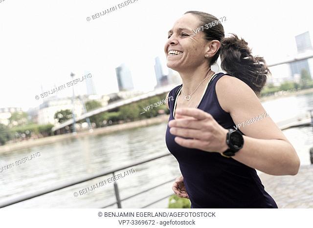 carefree woman enjoying jogging at river Main, in Frankfurt, Germany