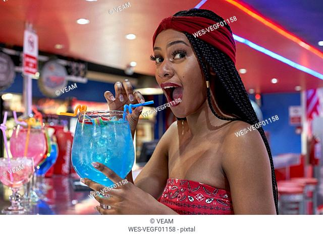 Young woman with braided hairstyle sitting on a restaurant's bar, drinking a blue cocktail