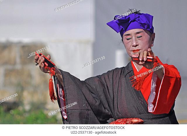 Itoman, Okinawa, Japan: a woman in traditional outfit dancing Okinawan music using sanba, a local instrument