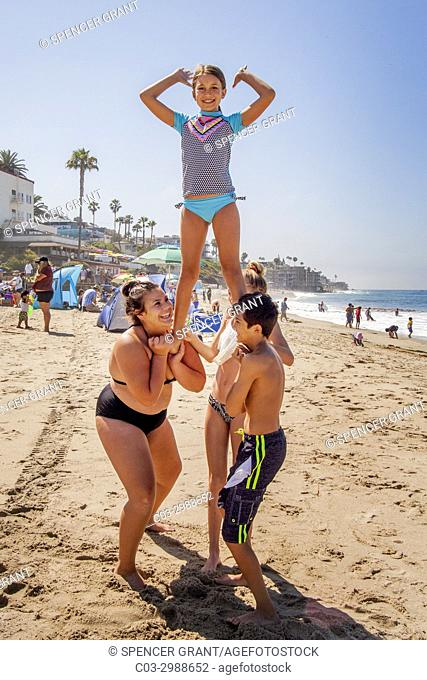 With the help of her son, a hefty Hispanic mom balances her tween daughter for a bounce on the sand at Laguna Beach, CA