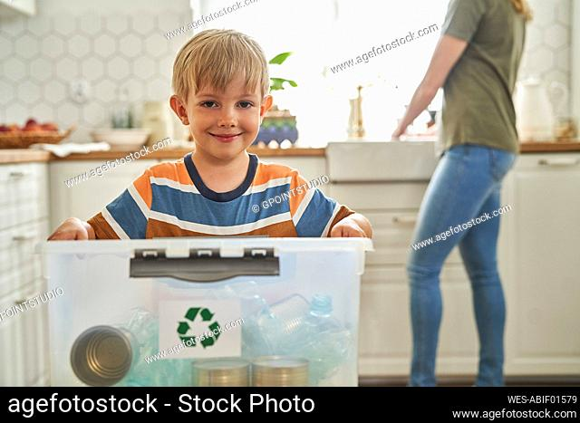 Smiling boy holding recycling container with bottles at home