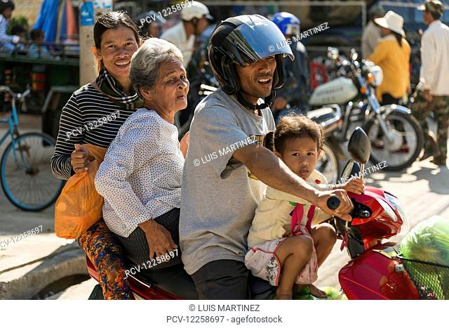 A family of four ride on a motorcycle at the Old Market; Battambang, Cambodia