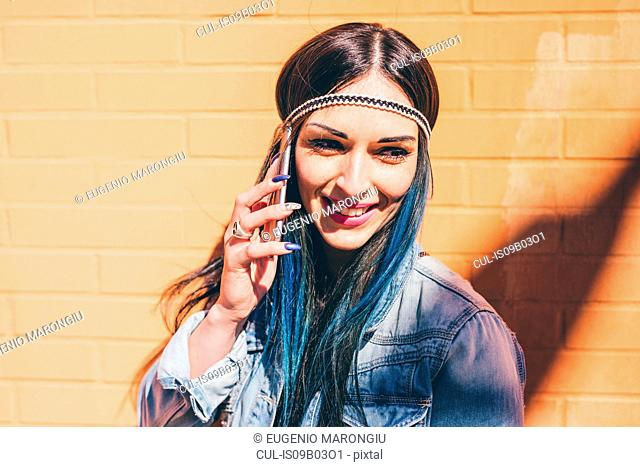 Young woman with dip dyed blue hair talking on smartphone in front of orange wall