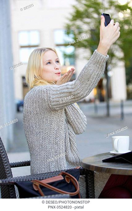 Pretty young woman doing a selfie in a Cafe in city center sending a kiss