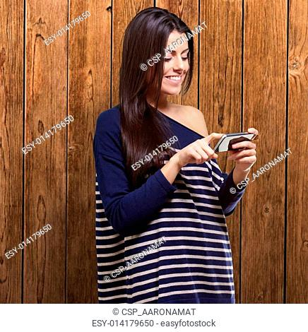 portrait of young woman touching a modern mobile against a wooden wall