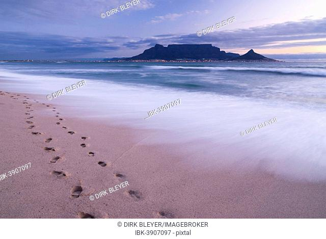 Table Mountain, Lion's Head and Devil's Peak in the evening light, panoramic view of Cape Town, footprints on Bloubergstrand beach