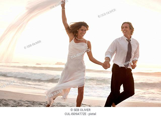 Bride and groom running on beach against sunset