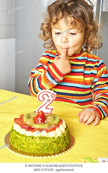 A two years old cacasian girl tasting her birthday cake