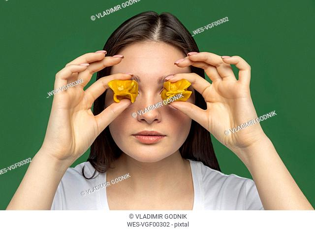 Portrait of young woman covering eyes with tortellini