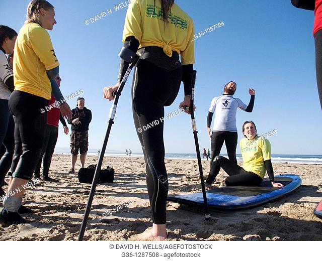 Surfers, teachers and volunteers gather to talk about the surfing at the end of the surf clinic sponsored by AmpSurf in Pismo Beach, California, United States