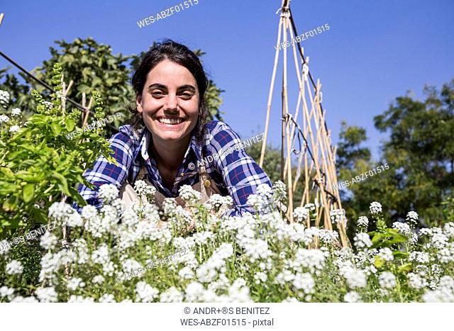 Happy woman working on farm, examining flowers