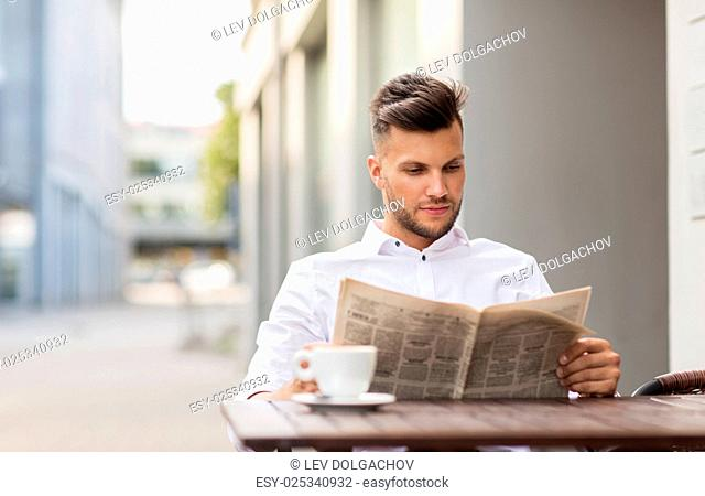 business, mass media and people concept - smiling man reading newspaper with coffee at city street cafe