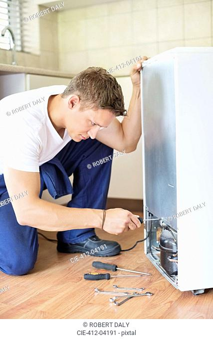 Repairman working on appliance in kitchen