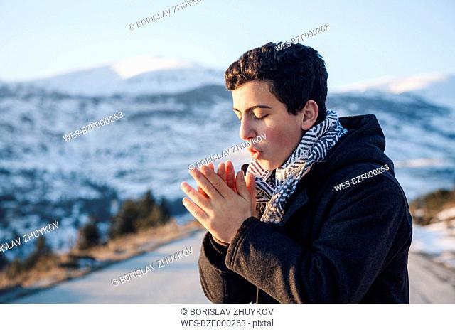 Teenage boy rubbing cold hands