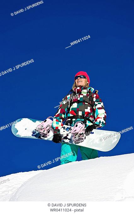 A snowboarder looks out over the snowy mountains with joy