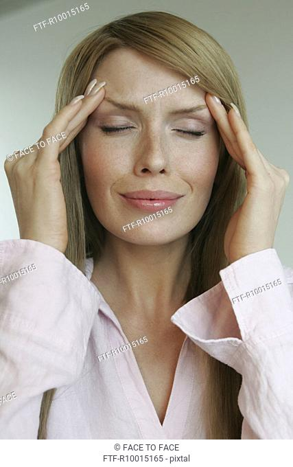 A blonde woman suffering from a severe headache