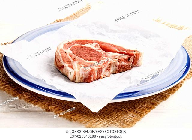 raw lamb chop with thyme on white kitchen paper and plate