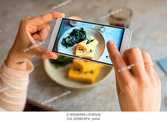 Woman taking photo of vegan meal