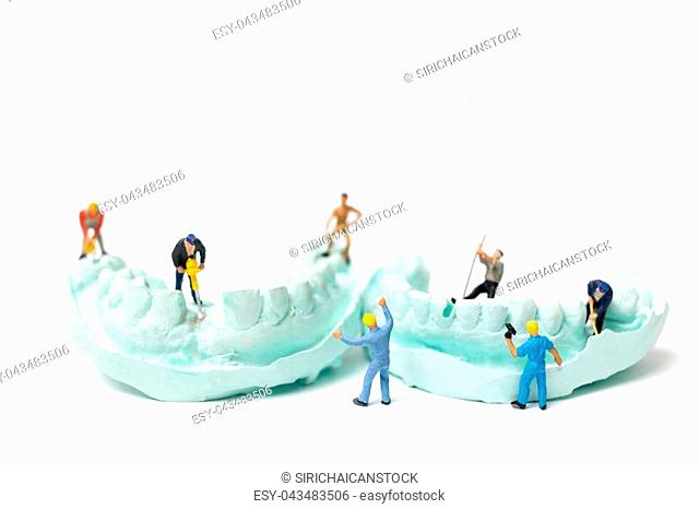 Miniature Worker team is filing fake teeth and placing them in a denture made with plaster