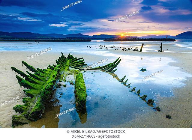 Tidal beach and boats remains at sunset. Santoña, Victoria and Joyel Marshes Natural Park. Colindres, Cantabria, Spain
