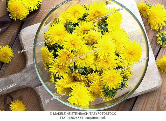 Yellow dandelion flowers in a bowl, top view