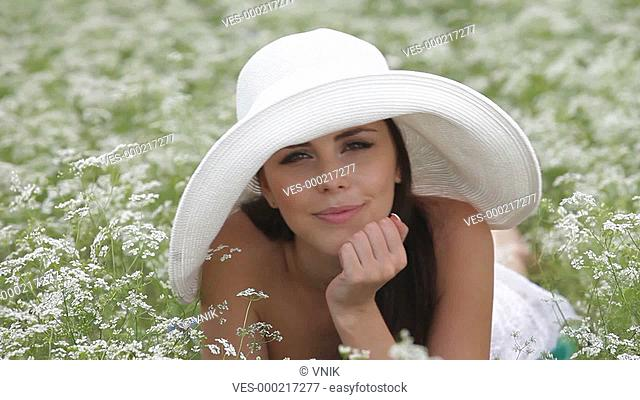Smiling Face Of a Young Woman In a Blossoming Field. Looking At Camera