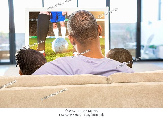 Composite image of two children sitting on sofa with their father