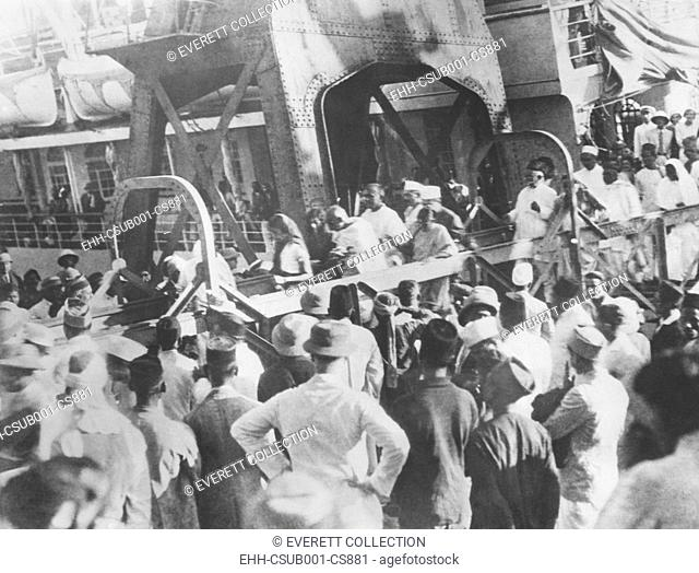 Mahatma Gandhi walking down the gangway arriving at Bombay, India, met by cheering thousands. He was returning from the 2nd London Roundtable Conference that...