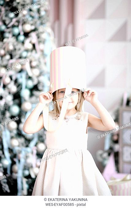 Portrait of smiling little girl with gift box on her head standing in front of lighted Christmas tree