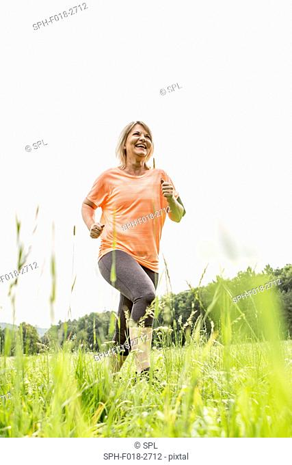 MODEL RELEASED. Mature woman jogging in grass