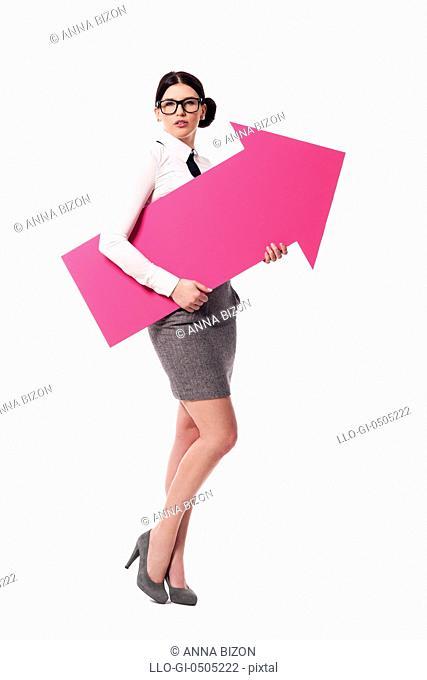 Gorgeous businesswoman holding pink arrow sign, Debica, Poland