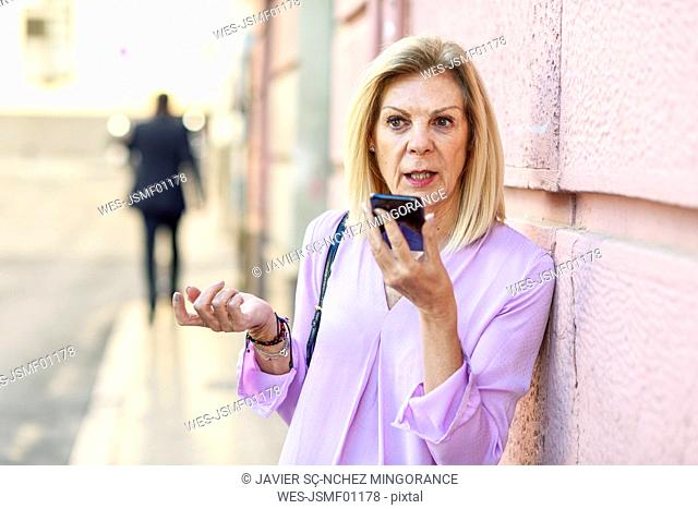 Mature woman using smartphone in the city