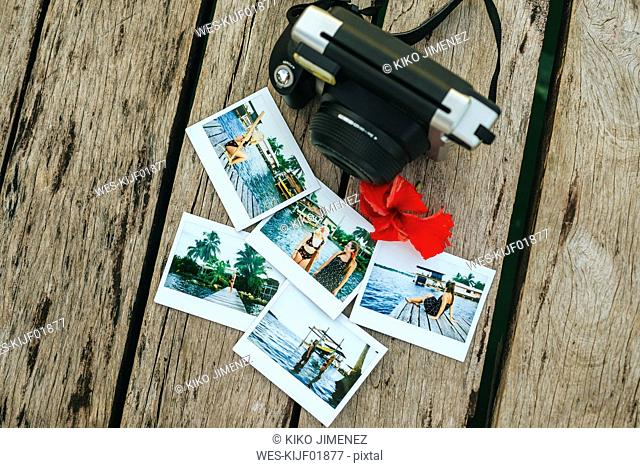 Panama, Bocas del Toro, Instant photographs and camera on wooden jetty