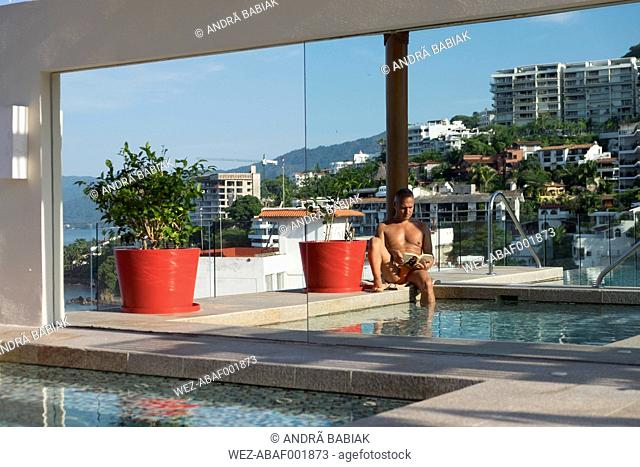 Mexico, Puerto Vallarta, man relaxing with book at the swimmingpool of a roof terrace